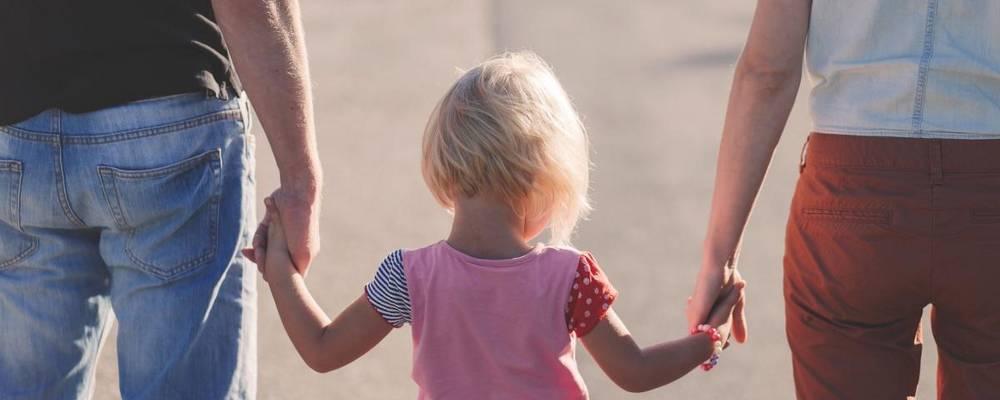Zwei Erwachsene, die ein Kind zwischen sich an den Händen halten