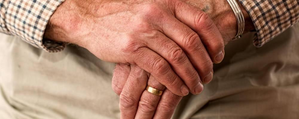 Hände auf einem Gehstock