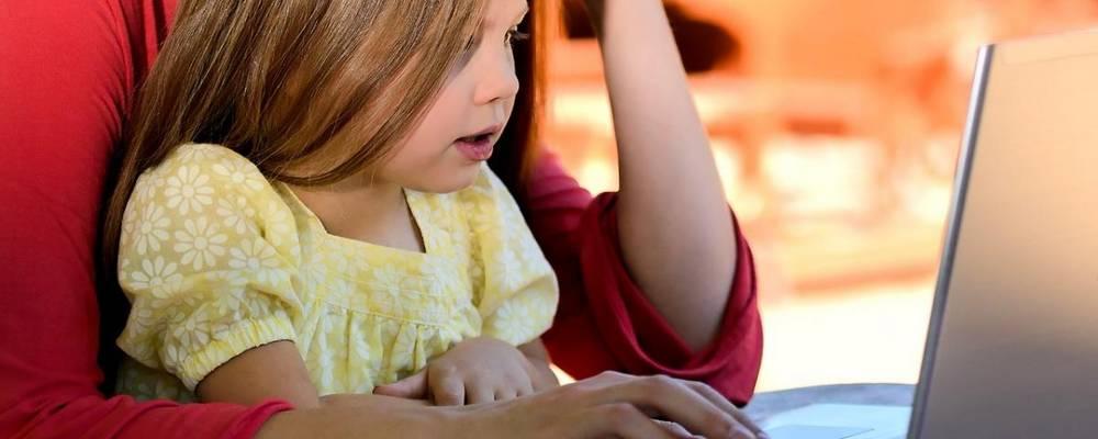 Ein Mädchen sitzt auf dem Schoß der Mutter und arbeitet am Laptop.