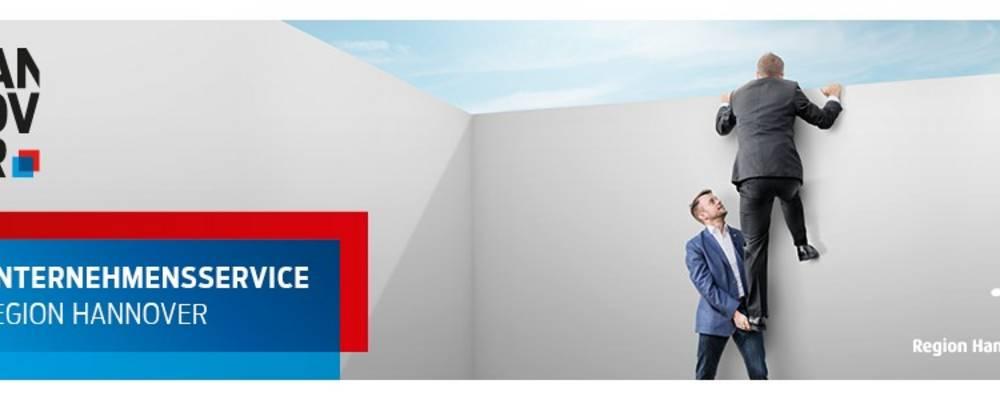 Logo der Region Hannover, der Wirtschaftsregion Hannover Zwei Männer welche mit Hilfer einer Räuberleiter eine Mauer überwinden [(c): Sabrina Deharde]