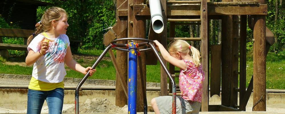 Zwei Mädchen auf einem Spielgerät, dahinter weitere Spileplatzbauten