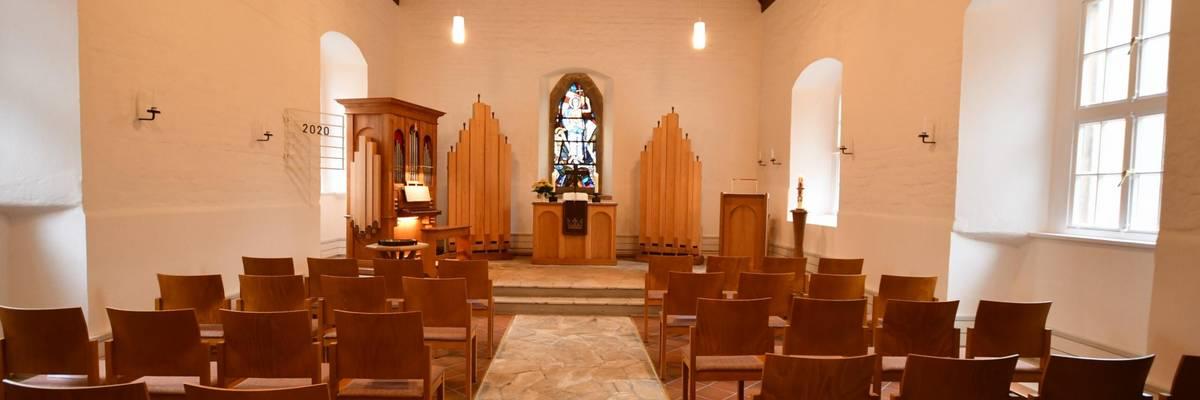 Blick über Gestühl zum Altarraum mit Altar, Orgel und Taufbecken