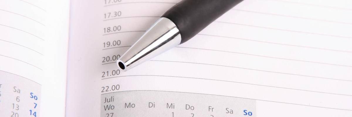 Ein Kugelschreiber liegt auf einem aufgeklappten Buchkalender.