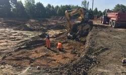 Bagger hebt den Boden aus zwei Bauarbeiter arbeiten in der Grube