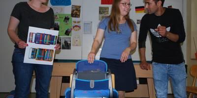 Zwei Sozialarbeiterinnen und der Dolmetscher zeigen Schulsachen.