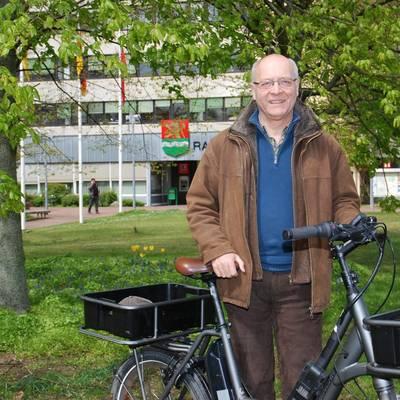 Bernd Rosenthal, Klimaschutzmanager der Stadt, steht mit einem Rad vor den Grünflächen vor dem Rathaus