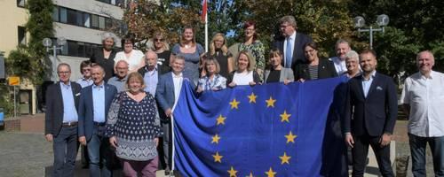 Die Delegationen zum Gruppenphoto auf dem Fritz-Willig-Brunnen vor dem Rathaus mit Europafahne [(c) Matthias Brinkmann]