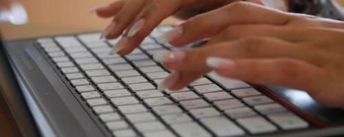 Es sind zwie Frauenhände zursehen, die auf einer Laptoptastatur tippen.