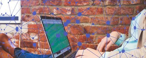 Eine Jugendliche hat die Beine hochgelegt und arbeitet an einem Laptop.