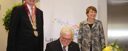 Steinmeier bei der Unterschrift, neben ihm seine Frau Elke Büdenbender und Bürgermeister Jürgen Köhne