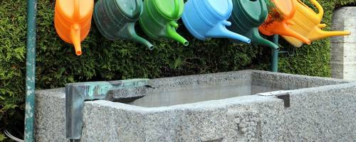 Bunte Kannen über einem Brunnen