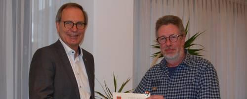 Jürgen Köhne und Alexander Muschal halten die verliehene Urkunde