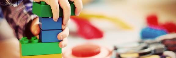 Kind baut einen Turm aus Bauklötzen