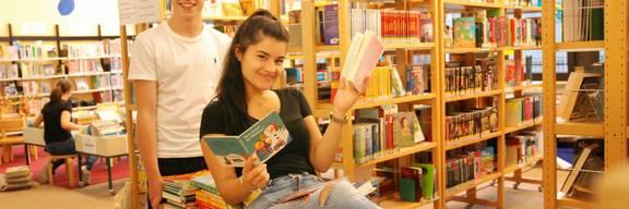 Junger Mann und junge Frau zwischen Bücherregalen