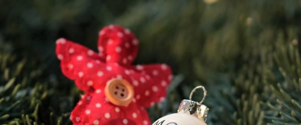 Kleiner Weihnachtsengel aus rotem Stoof mit Knop und eine kleine weiße Christbaumkugel mit 'Merry Xmas' ©Pixabay