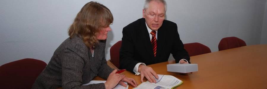 Eine Frau und ein Mann in Buisnesskleidung sitzen gemeinsam an einem Tisch und gehen Informationsmaterial durch