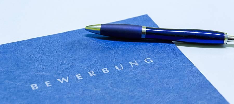 Blaue Bewerbungsmappe mit Stift