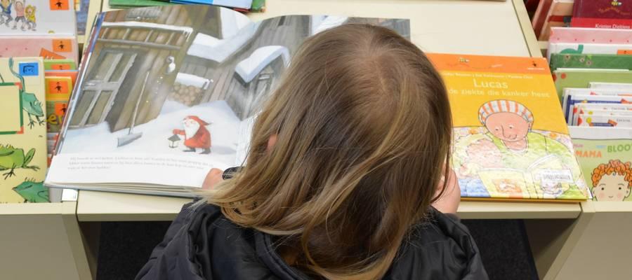 Mädchen von hinten fotografiert, schaut sich ein Buch an