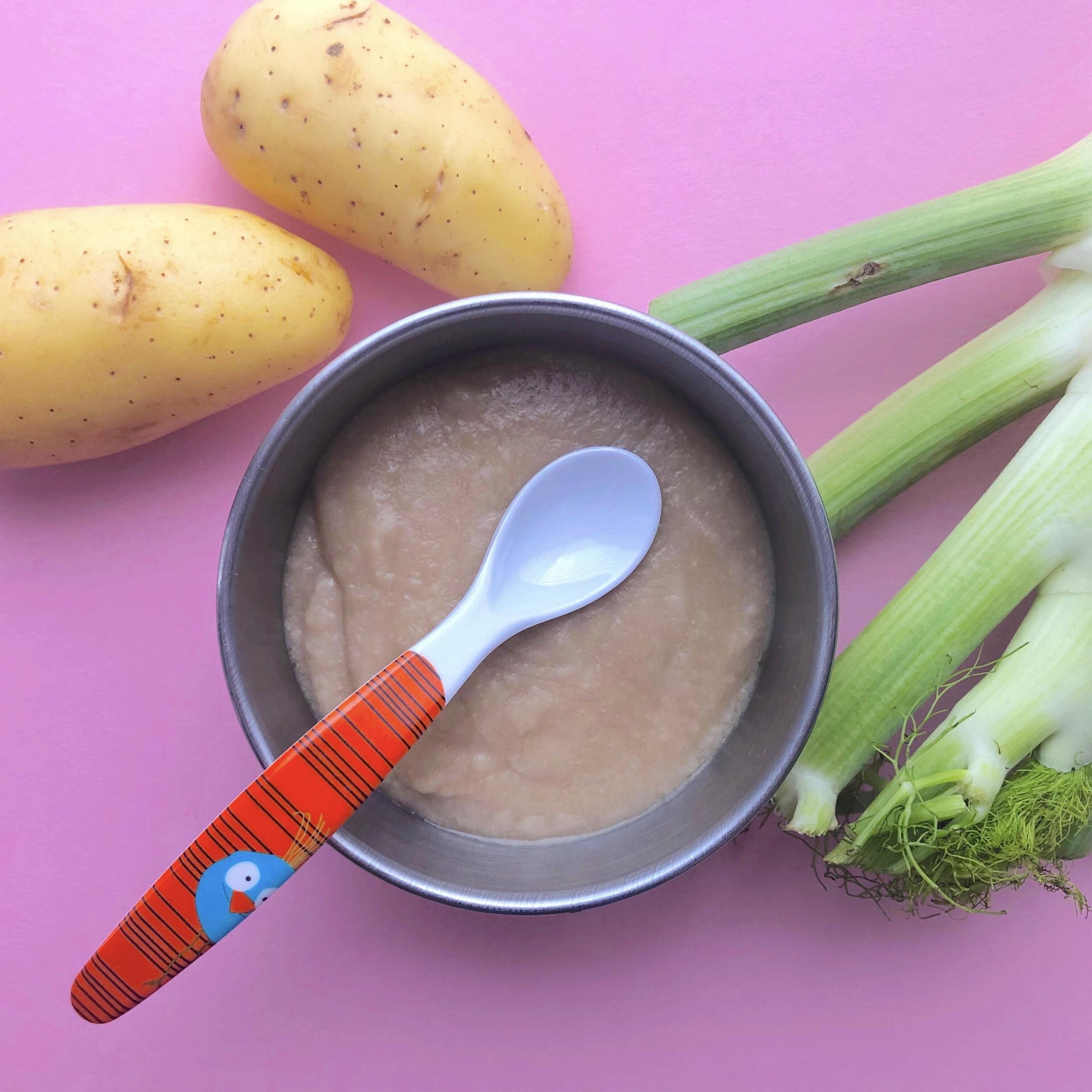 Schale mit Brei und Löffel, daneben Fenchel und Kartoffeln