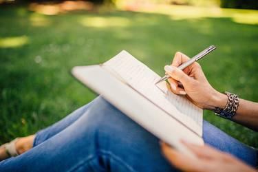 Junge Frau schreibend auf einer Wiese