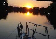 Bootsspitze auf dem  Fluss mit Sonnenuntergang im Hintergrund