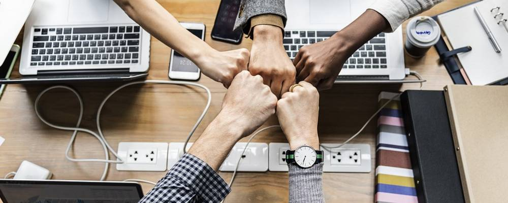 Hände, die über einen Schreibtisch einen Stern bilden