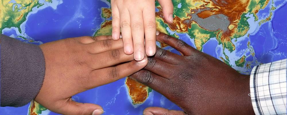 Drei Hände unterschiedlicher Hautfarbe halten sich über einer Weltkarte an den Händen [(c): Ilka Hanenkamp-Ley]