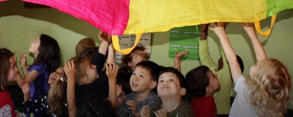 Kinder unter einem Schwungtuch