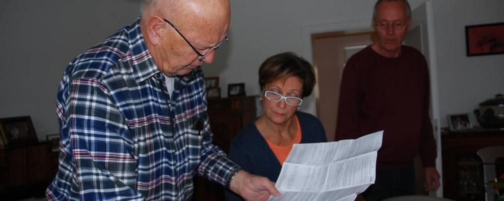 Senioren lesen gemeinsam eine Bedienungsanleitung