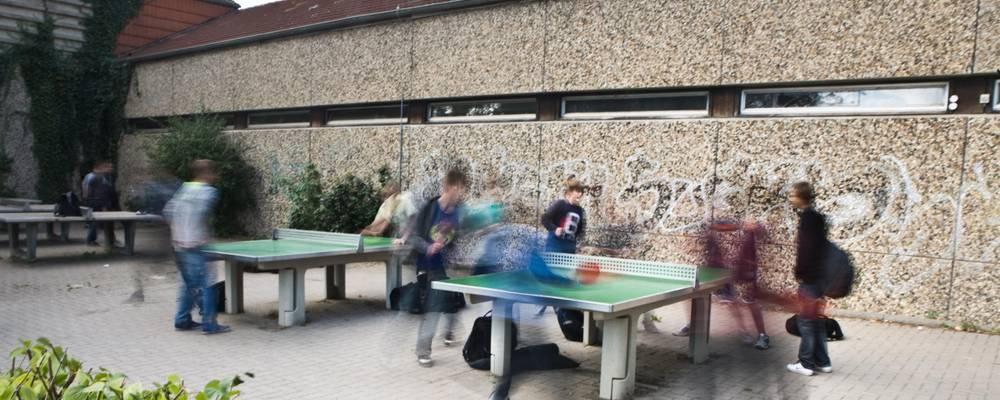 Kinder spielen auf dem Schulhof Tischtennis