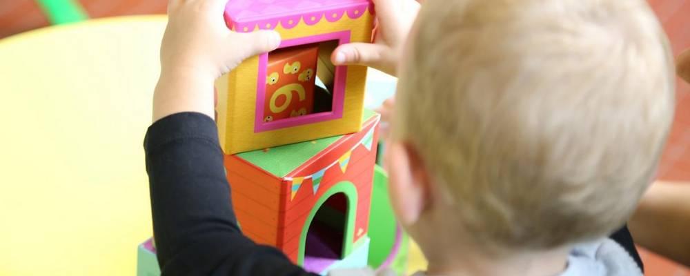Kind in Rückenansicht spielt mit Bauklätzen