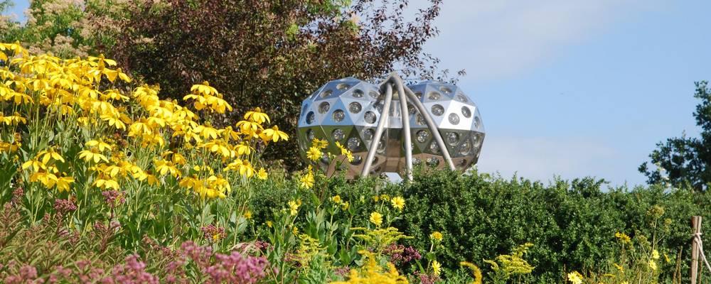 Kunstobjekt vor blühenden Sommerblumen