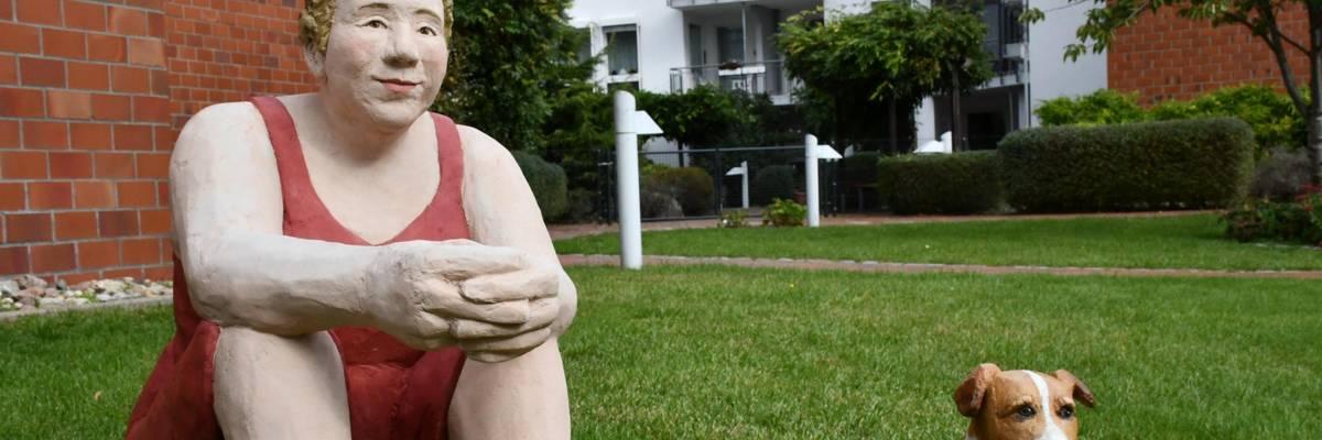 Skulptur einer Frau und eines Hundes auf einer Wiese
