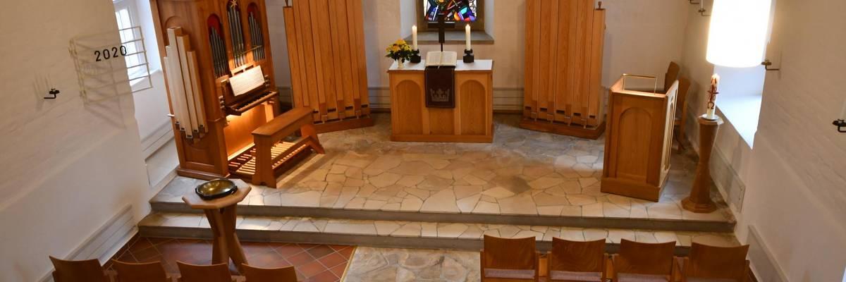 Blick von oben in das Innere der Kappele mit Stühlen und Altar