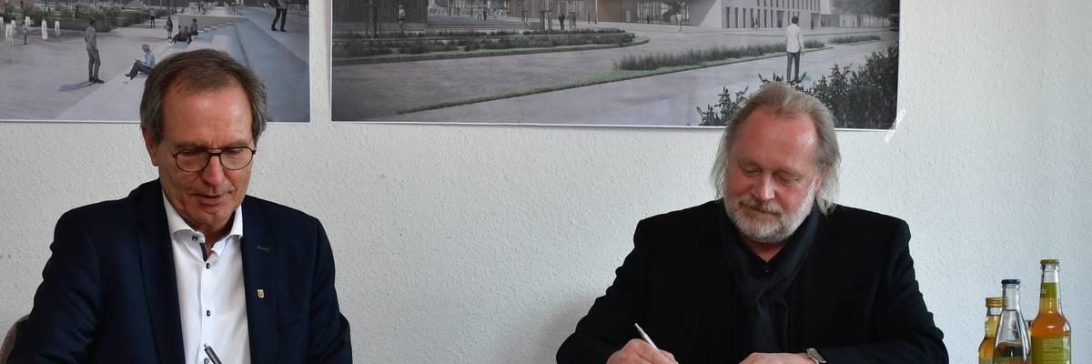 Zwei Herrn sitzen in einem Raum am Tisch, hinter ihnen an der Wand hängen Grundrisse des neuen Gebäudes. Für dieses unterschreiben beide den Vertrag. ©Stadt Laatzen/Ilka Hanenkamp-Ley