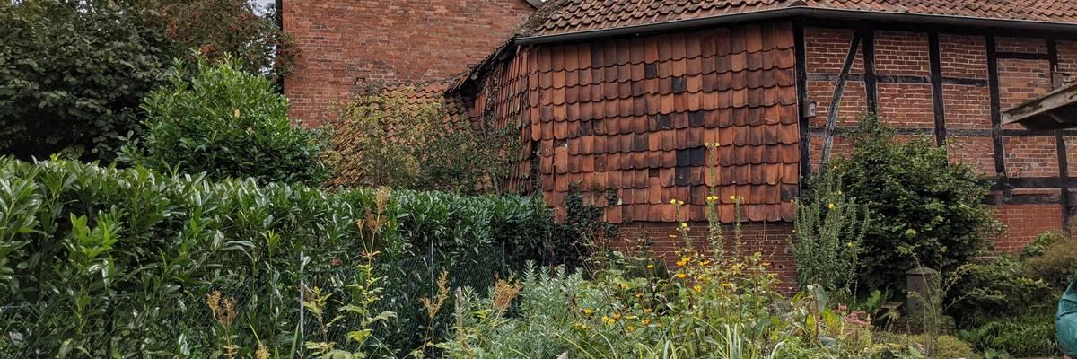 Ein rot gemauertes Fachwerkhaus. Davor befindet sich ein Garten mit Blüten und Gräsern. ©Stadt Laatzen/Ilka Hanenkamp-Ley