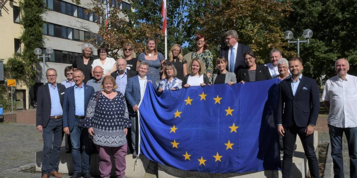 Die Delegationen zum Gruppenphoto auf dem Fritz-Willig-Brunnen vor dem Rathaus mit Europafahne