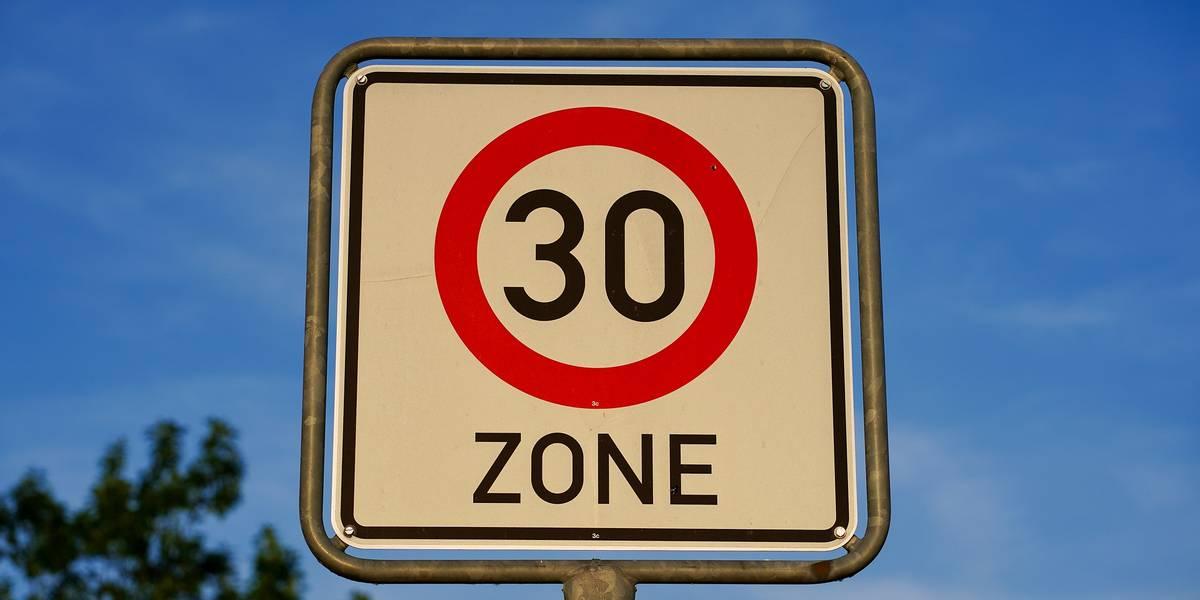 Schild vor blauem Himmel mit einer roten 30