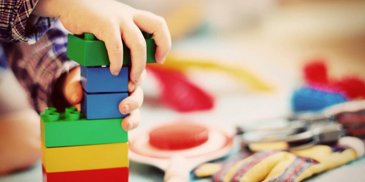 Kind mit Bauklötzen baut einen Turm. Man sieht die Händer, die gerade einen neuen Bauklotz festdrücken.