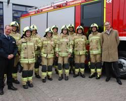 Kameradinnen und Kameraden der Laatzener Feuerwehr mit den neuen Helmen vor dem LF. Daneben Stadtbrandmeister Sebastian Osterwald und Bürgermeister Jürgen Köhne. [(c): Stadt Laatzen]