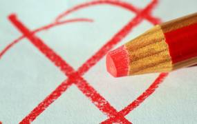 Roter Kreis mit rotem Kreuz. An der Seite ist ein roter Buntstift zu sehen.