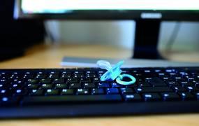 Ein Schnuller liegt auf einer Computertastatur.