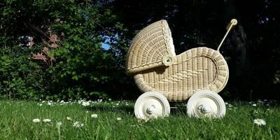 nostalgischer Puppenwagen auf einer grünen Wiese