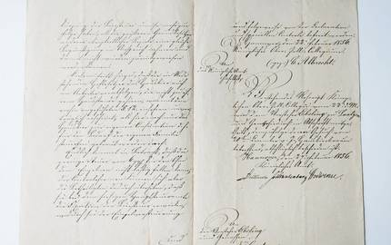 Aufgeschlagenes Buch, eine historosche Handschrift auf vergilbtem Papier ist zu sehen.