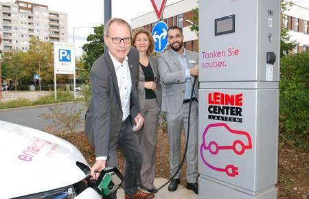 Bürgermeister Jürgen Köhne betakt ein E-Auto am Leinecenter. Dahinter Dr. Susanne Zapreva und Guillermo Poveda. [(c) Matthias Brinkmann]
