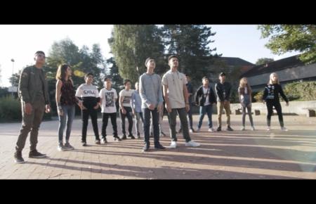 Gruppe von Jugendlichen steht auf einem Schulhof