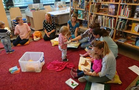 Mütter sitzen mit ihren Kleinkindern auf einem Teppich und schauen sich Bücher an.