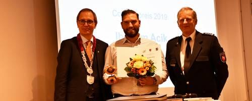 Gruppe von drei Menschen, in der Mitte hält der Preisträger eine Urkunde und seinen Preis in die Höhe