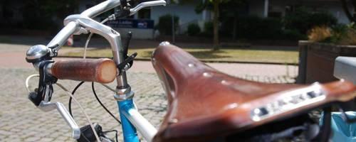 Ein älteres Fahrrad steht auf dem Marktplatz, verschwommen im Hintergrund kann man das Stadteilbüro erahnen.