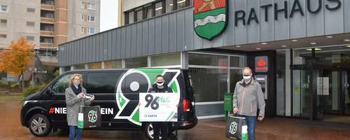 Maskenübergabe vor dem Rathaus mit Hannover 96-Bulli